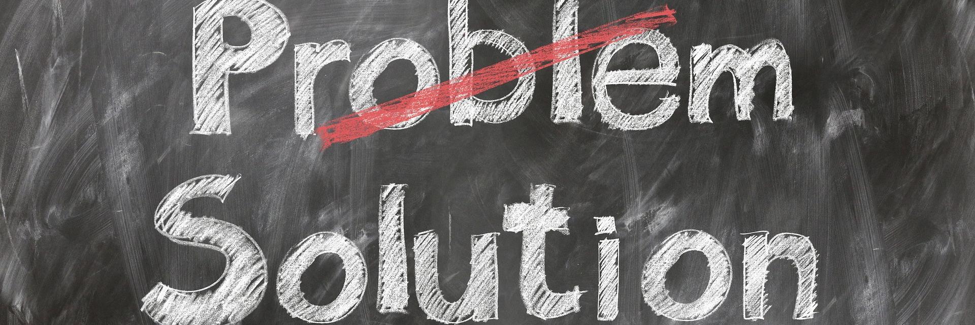 """Liitutaululle kirjoittetu sana """"Problem"""" joka on yliviivattu ja sen alle kirjoitettu """"Solution""""."""
